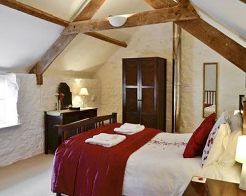 A well furnished bedroom with a vaulted ceiling.
