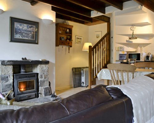 A well furnished living room with a fire in the fireplace dining area open plan kitchen and wooden stairway.