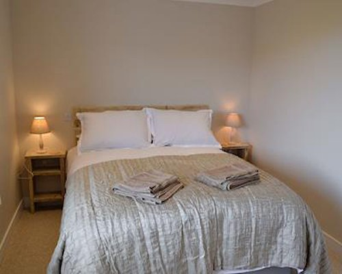 A well furnished bedroom with lampshades.
