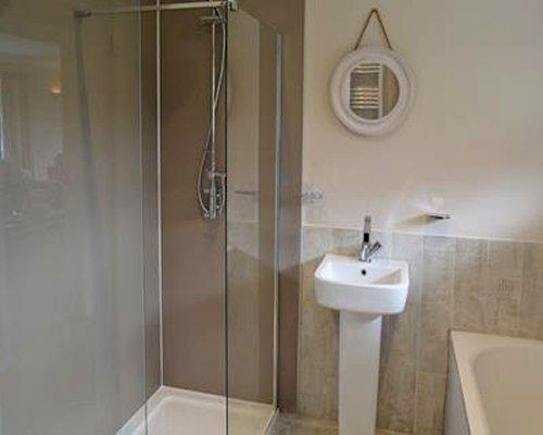 A bathroom with a sink bathtub and a shower stall.