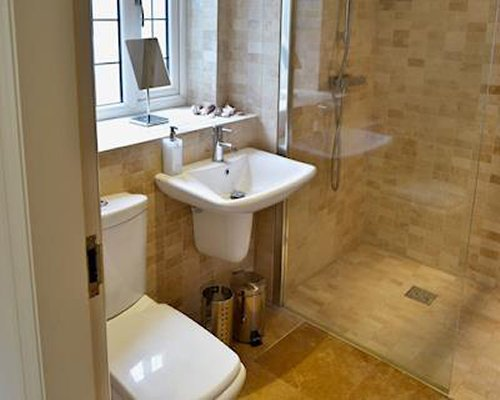 A bathroom with stand up shower and sink.