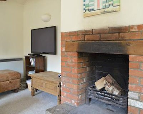 A room with a television and fireplace.