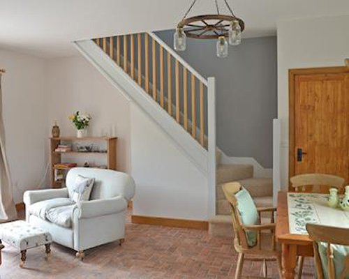 A well furnished living and dining area with a staircase.
