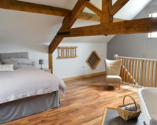 A well furnished bedroom with bathtub stairway and vaulted ceiling.