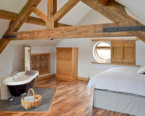 A well furnished bedroom with bathtub and vaulted ceiling.