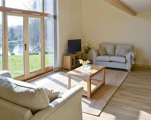 A well furnished living room with a television double pull out sofas and an outside view.