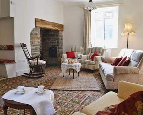 A well furnished living room with fireplace and outside view.