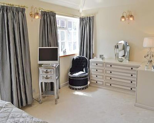 A well furnished bedroom with television and outside view.
