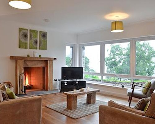An open plan furnished living and dining area with a television and fire in the fireplace.