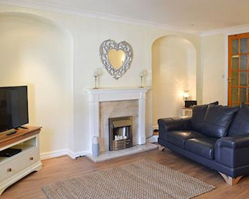 An open plan dining area and living room with a fire in the fireplace.