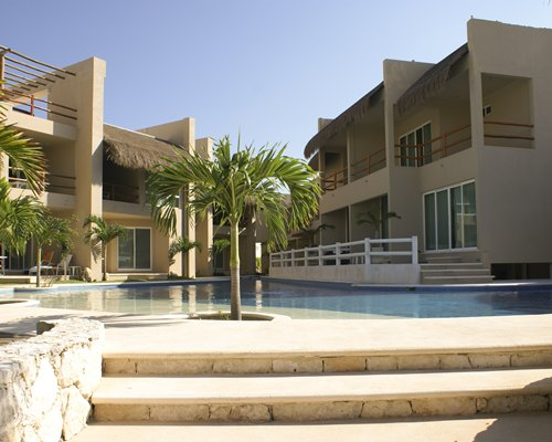 An outdoor swimming pool with palm trees alongside the resort unit.
