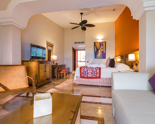 A well furnished living room with an open plan bedroom and television.