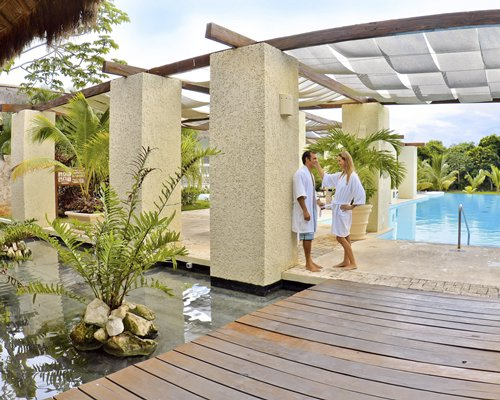 A couple standing near the outdoor swimming pool.
