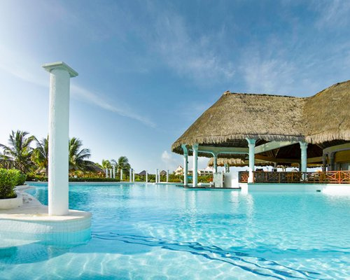 Large outdoor swimming pool alongside a thatched covered restaurant.