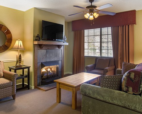 A well furnished living room with a television fireplace stairway indoor balcony and outside view.