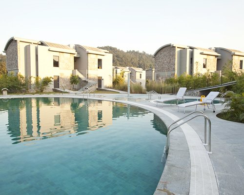 An outdoor swimming pool and hot tub with chaise lounge chairs alongside the resort units.