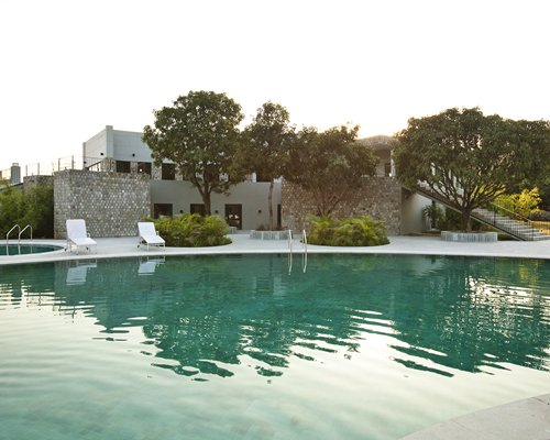 An outdoor swimming pool with chaise lounge chairs alongside resort unit and trees.
