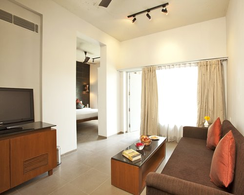 A well furnished living room with a television alongside a bedroom.