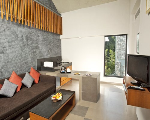 A well furnished living room with a television open plan kitchen and outside view.