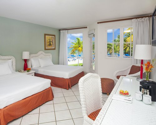 A well furnished bedroom with two twin beds balcony and beach view.