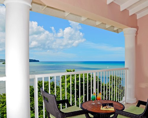 View of the ocean from the balcony with patio furniture.