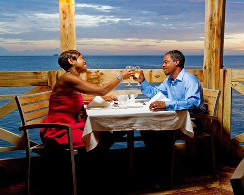 A couple at an outdoor dining area alongside the ocean.