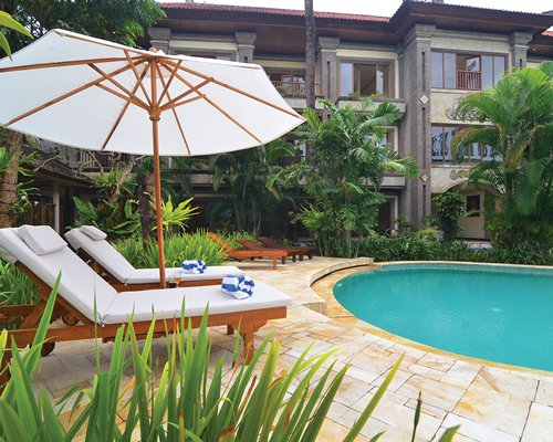 A scenic outdoor swimming pool with chaise lounge chairs and sunshade alongside multi story units.