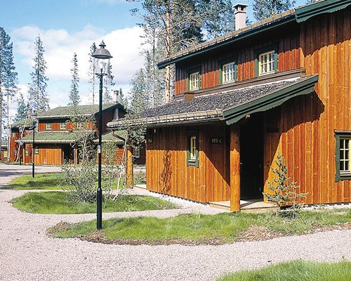 Multiple vacation units surrounded by pathways lawns and trees.