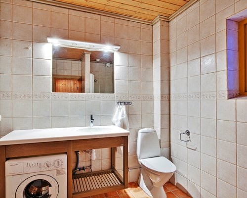 A bathroom with a single sink vanity and washing machine.