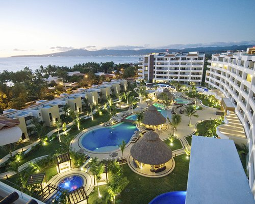 Marival Residences Luxury Resort with an outdoor swimming pool and hot tub alongside the ocean.