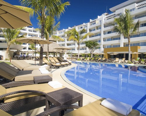 An outdoor swimming pool with chaise lounge chairs and sunshades alongside the multi story unit.
