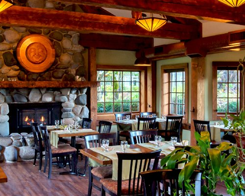 An indoor fine dining restaurant with a fire in the fireplace and an outside view.