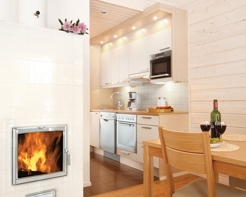An open plan kitchen and dining area with fire in the fireplace.