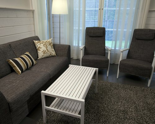 A well furnished living room with sofas and an outside view.