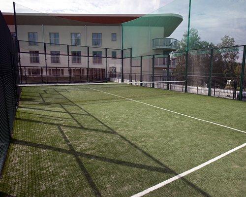 An outdoor tennis court alongside resort units.