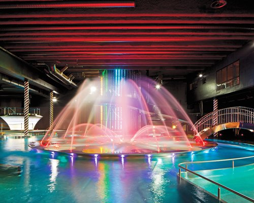 A view of an indoor swimming pool with a dancing fountain.