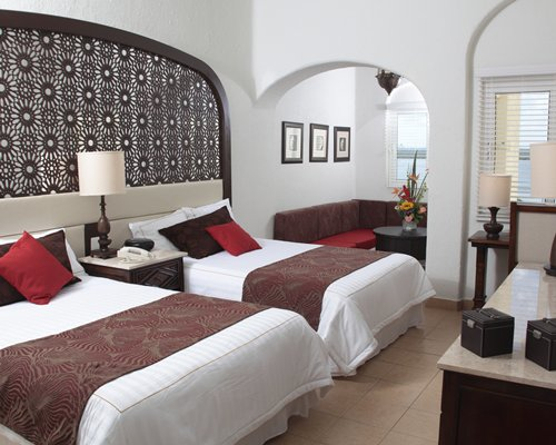 A wll furnished bedroom with two double beds.
