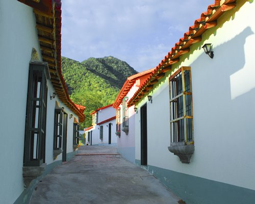Exterior view of a pathway to units at Hotel Hacienda El Portete alongside the mountains.