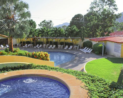 An outdoor hot tub and swimming pool with chaise lounge chairs and landscaping.