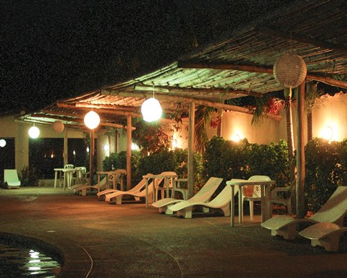 View of chaise lounge chairs alongside the pool at night.