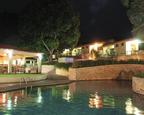An outdoor swimming alongside the resort units at night.