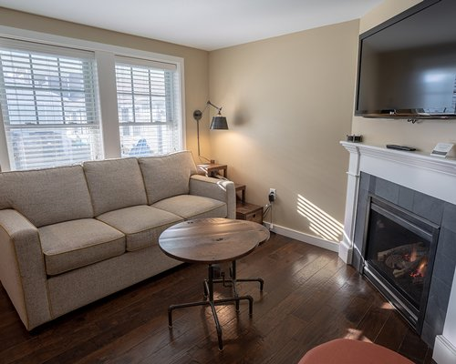 A well furnished living room with a television pull out sofa fire in the fireplace and an outside view.