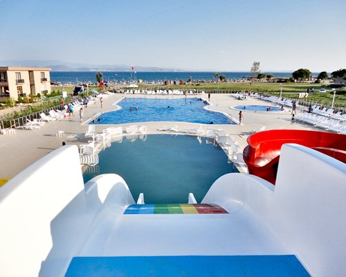 An outdoor swimming pool with a hot tub slide and chaise lounge chairs alongside the sea.