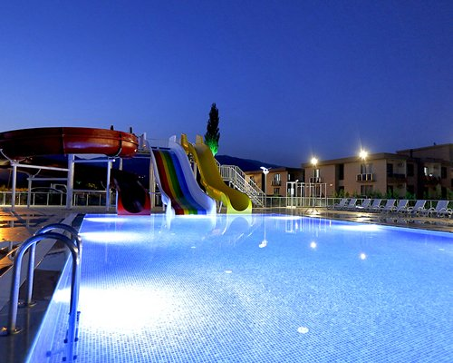 An outdoor swimming pool with chaise lounge chairs and water slide.