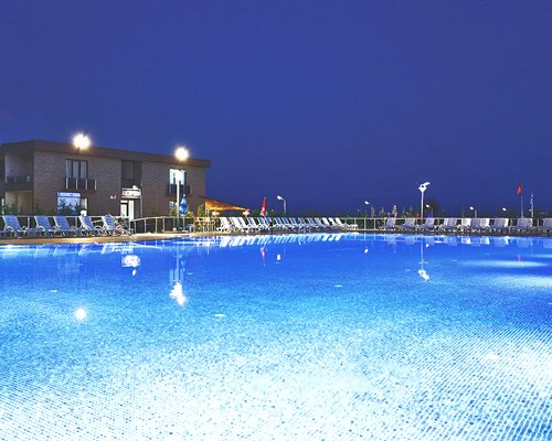 Night view of a large outdoor pool with chaise lounge chairs alongside the resort.