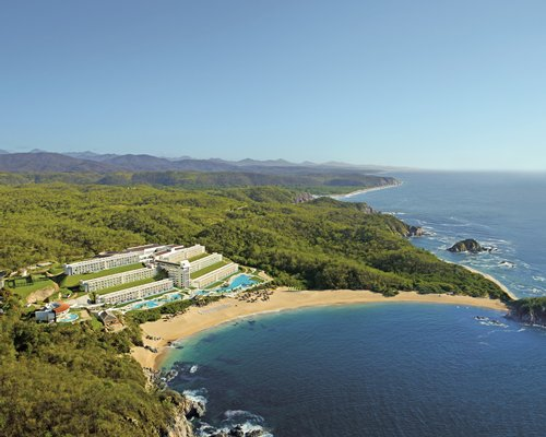 An aerial view of Secrets Huatulco Resort and Spa surrounded by wooded area alongside the ocean.