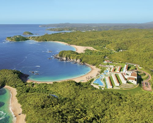 An aerial view of Secrets Huatulco Resort & Spa alongside the beach and ocean at a wooded area.