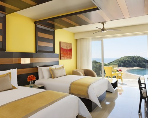 A well furnished bedroom with two twin beds and an outdoor patio alongside the beach.