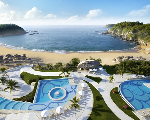 View of outdoor swimming pool alongside the ocean.