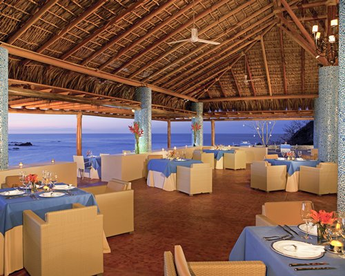 Thatched covered outdoor restaurant alongside the ocean.